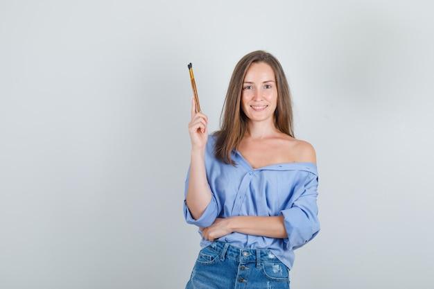 Jeune femme tenant des pinceaux en chemise, short et à la joyeuse