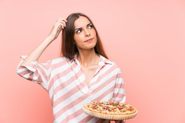 Jeune femme tenant une pizza sur un mur rose isolé ayant des doutes et avec une expression de visage confuse