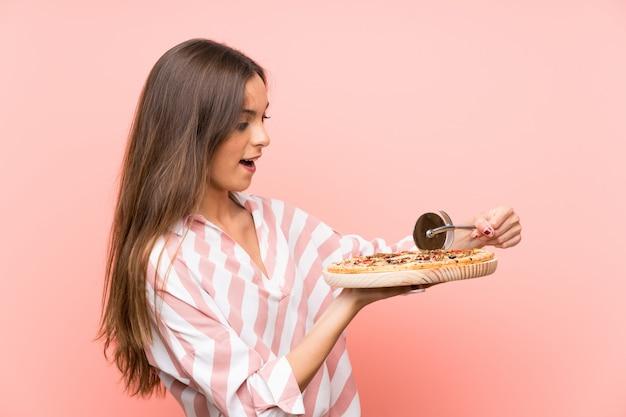 Jeune femme tenant une pizza
