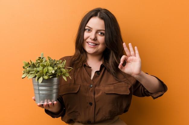 Jeune femme tenant une plante gaie et confiante montrant le geste ok.
