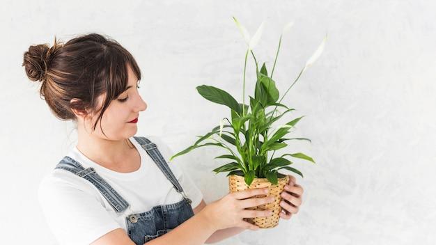 Jeune femme tenant une plante en pot