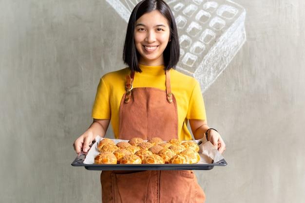 Jeune femme tenant un plateau avec de la crème fraîche de choux ou un éclair.