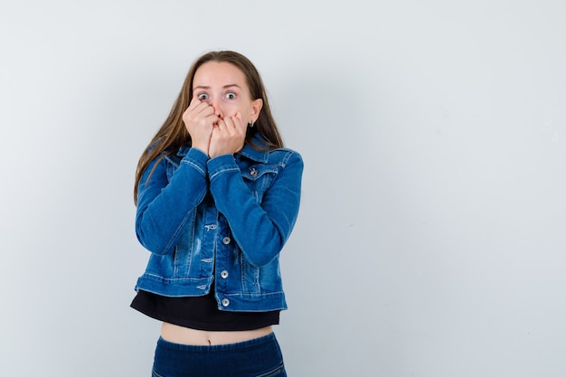 Jeune femme tenant les poings sur la bouche en blouse, veste et l'air effrayé, vue de face.