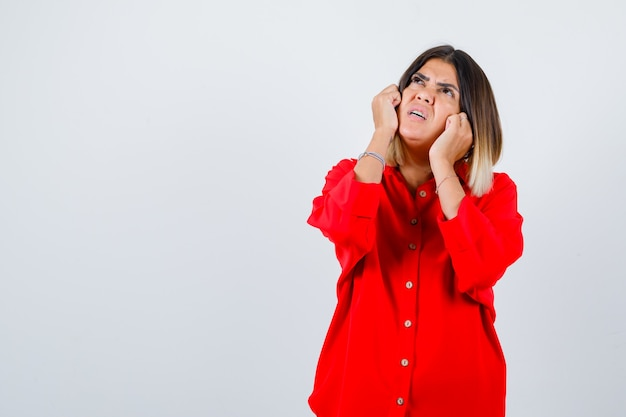 Jeune femme tenant les poings sur les joues en chemise rouge surdimensionnée et regardant attentivement. vue de face.