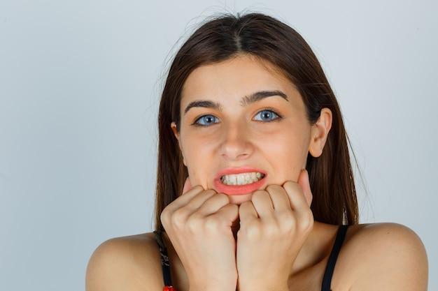 Jeune femme tenant les poings sur le menton en blouse et à la peur. vue de face.