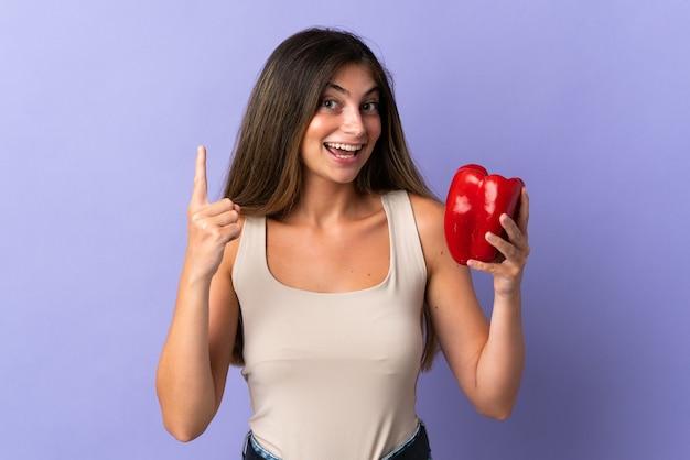 Jeune femme tenant un poivron isolé sur violet pointant vers le haut une excellente idée