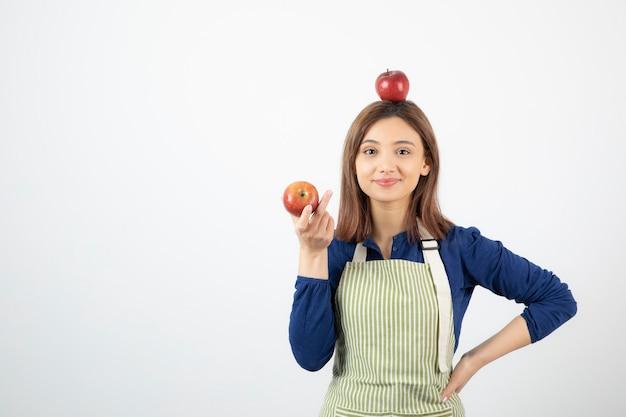 Jeune femme tenant des pommes rouges en souriant sur fond blanc.