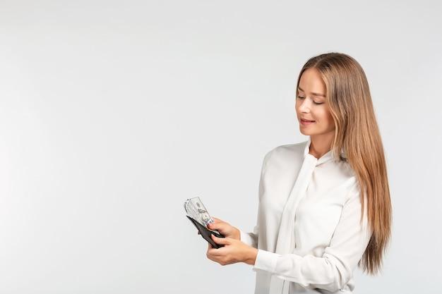 Jeune femme tenant un portefeuille avec des billets en dollars sur fond clair