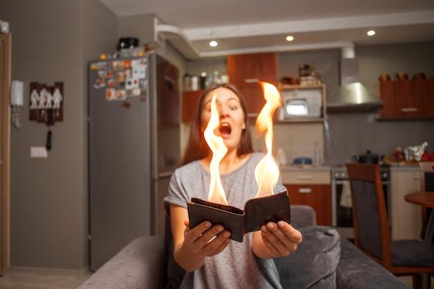 Jeune femme tenant un portefeuille, portefeuille en feu, fille surprise, focus concept magique