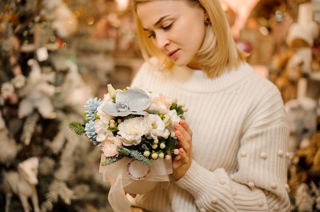 Jeune femme tenant un pot de fleur avec des fleurs blanches décorées avec des feuilles vertes et des branches de sapin