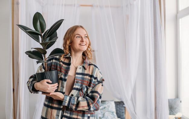 Jeune femme tenant un pot de fleurs dans un nouvel appartement dans la joie après avoir emménagé. une jolie jeune fille apporte un pot vert dans une nouvelle maison. concept de location ou d'achat