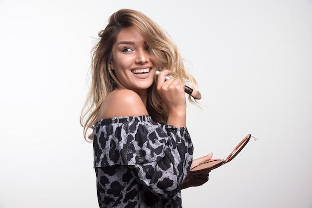 Jeune femme tenant une poudre bronzante et une brosse.