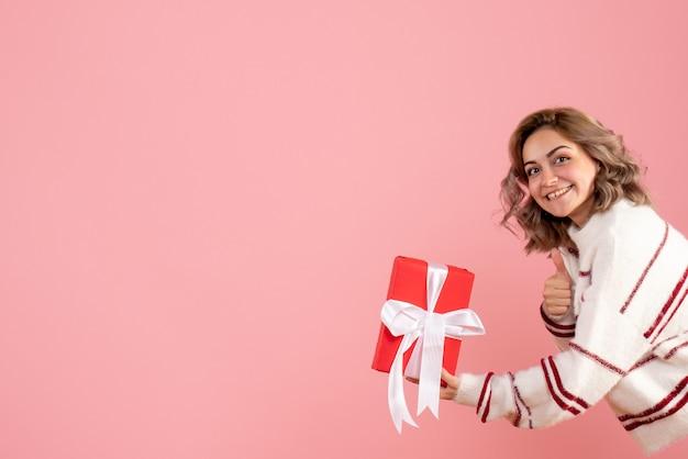 Jeune femme tenant présent sur rose