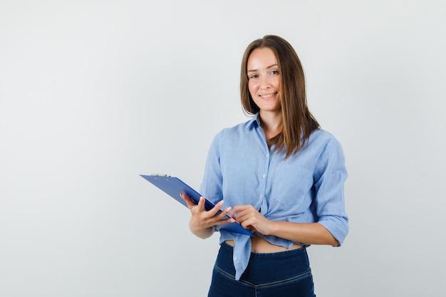 Jeune femme tenant le presse-papiers en chemise bleue, pantalon et à la joyeuse