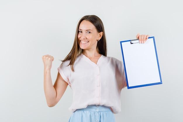 Jeune femme tenant le presse-papiers avec le geste gagnant en t-shirt, jupe et à la joyeuse. vue de face.