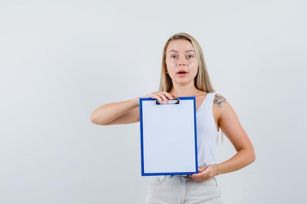Jeune femme tenant le presse-papiers vierge en chemisier blanc et à la recherche concentrée