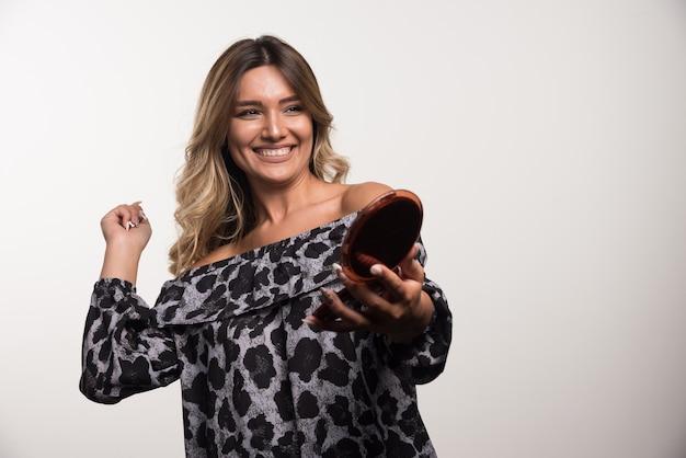 Jeune femme tenant un produit cosmétique en souriant sur un mur blanc.