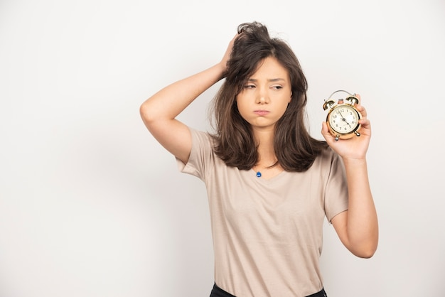 Jeune femme tenant un réveil sur fond blanc.