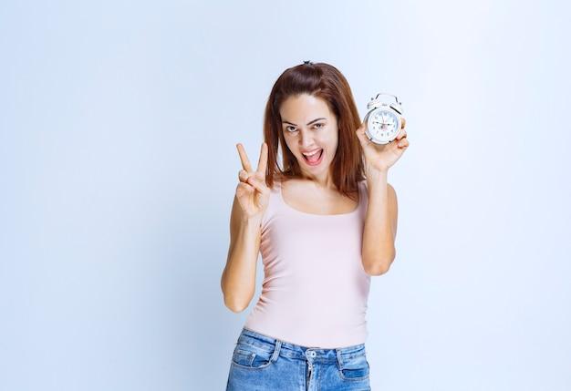 Jeune femme tenant un réveil et le pointant du doigt