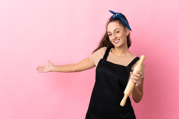 Jeune femme tenant un rouleau à pâtisserie étendant les mains sur le côté pour inviter à venir