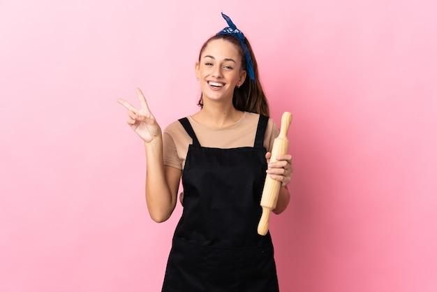 Jeune femme tenant un rouleau à pâtisserie souriant et montrant le signe de la victoire