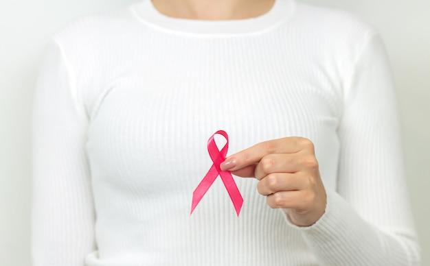 Jeune femme tenant un ruban rose de sensibilisation au cancer du sein. concept de la journée mondiale du cancer