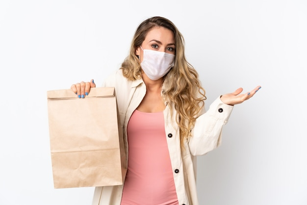 Jeune femme tenant un sac d'épicerie isolé sur blanc avec une expression faciale choquée