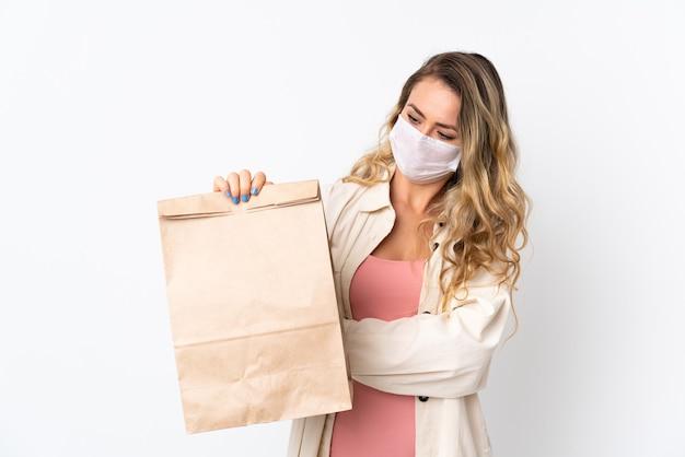 Jeune femme tenant un sac d'épicerie isolé sur blanc avec une expression triste