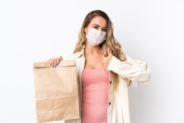 Jeune femme tenant un sac d'épicerie isolé sur blanc avec les pouces vers le haut parce que quelque chose de bien s'est passé