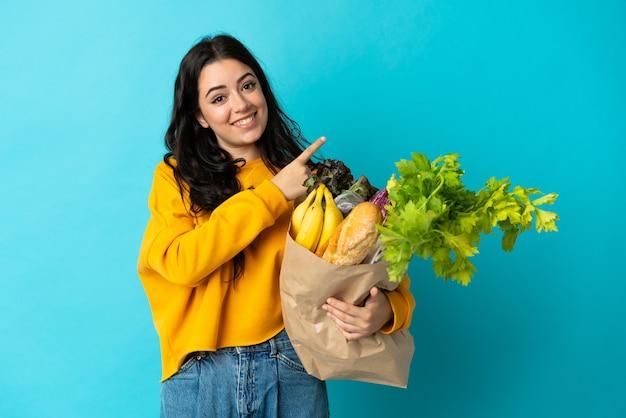 Jeune femme tenant un sac d'épicerie isolé sur bleu pointant vers le côté pour présenter un produit