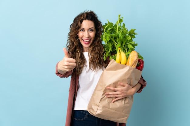 Jeune femme tenant un sac d'épicerie isolé sur bleu avec les pouces vers le haut parce que quelque chose de bien s'est passé