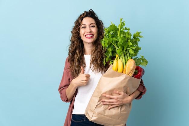 Jeune femme tenant un sac d'épicerie isolé sur un mur bleu donnant un geste de pouce en l'air