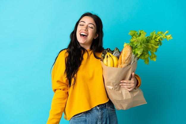 Jeune femme tenant un sac d'épicerie isolé sur mur bleu en riant
