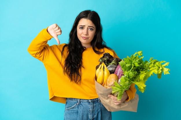 Jeune femme tenant un sac d'épicerie isolé