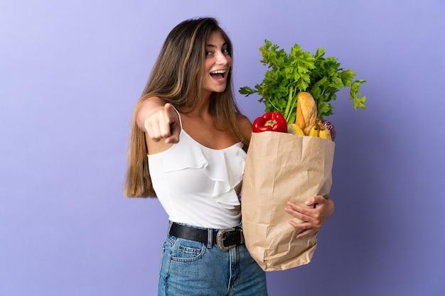 Jeune femme tenant un sac d'épicerie pointant vers l'avant avec une expression heureuse