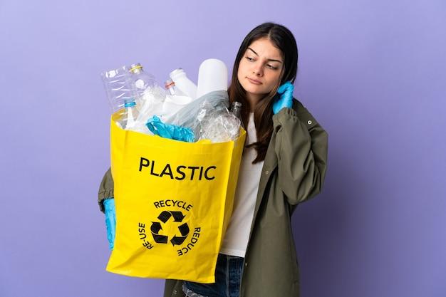 Jeune femme tenant un sac plein de bouteilles en plastique à recycler isolé sur mur violet ayant des doutes