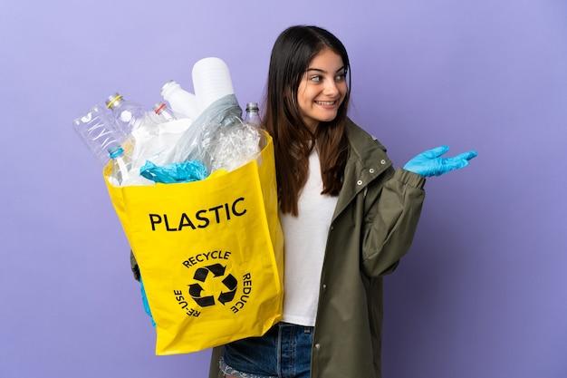 Jeune femme tenant un sac plein de bouteilles en plastique à recycler isolé sur mur violet étendant les mains sur le côté pour inviter à venir