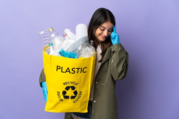Jeune femme tenant un sac plein de bouteilles en plastique à recycler isolé sur mur violet en riant