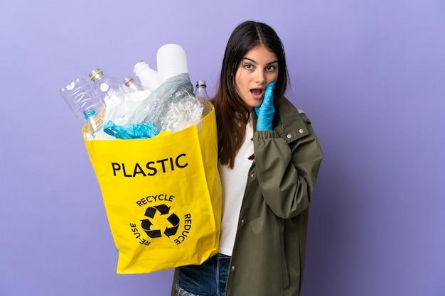 Jeune femme tenant un sac plein de bouteilles en plastique à recycler isolé sur violet avec surprise et expression du visage choqué