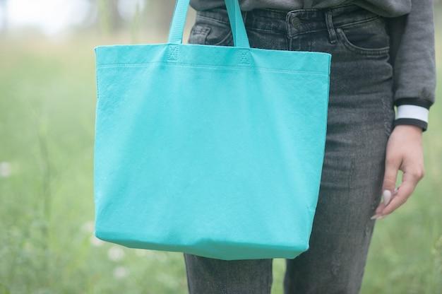 Jeune femme tenant un sac shopper vert émeraude, pas de visage, concept de mode de vie écologique