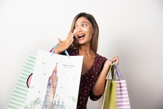 Jeune femme tenant des sacs sur le mur blanc.