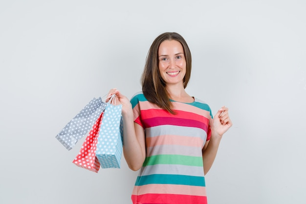 Jeune femme tenant des sacs en papier en t-shirt et à la joyeuse vue de face.