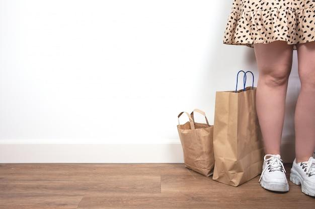 Jeune femme tenant des sacs à provisions, debout contre un mur blanc, design moderne aux couleurs naturelles. concept rétro