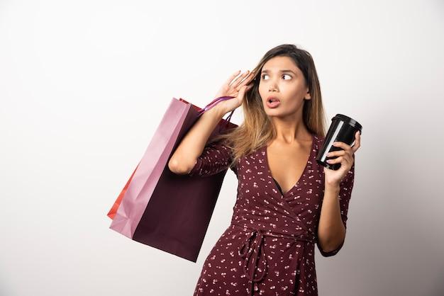 Jeune femme tenant des sacs et une tasse de boisson sur un mur blanc.