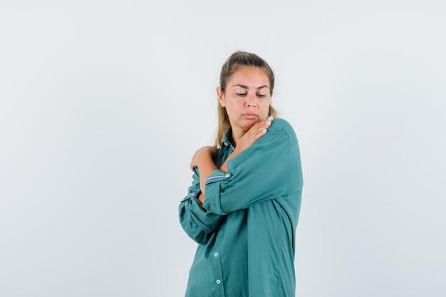 Jeune femme tenant ses mains croisées sur ses épaules en chemise bleue et à la satisfaction