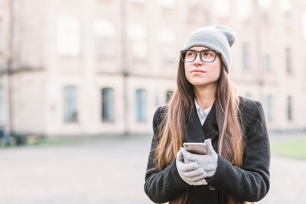 Jeune femme tenant un smartphone dans la rue