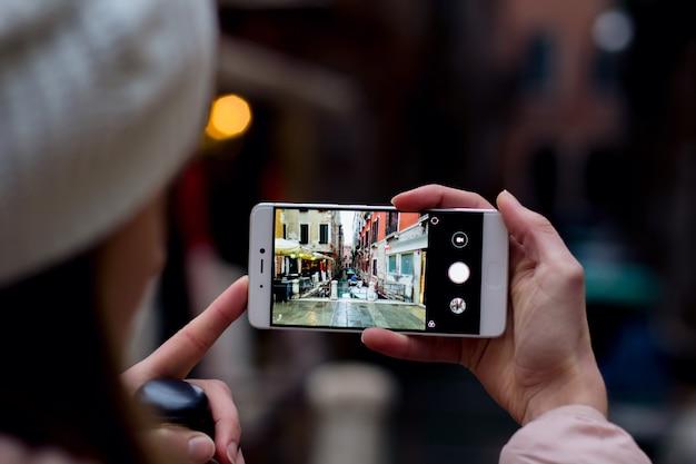 Jeune femme tenant un smatphone et prenant une photo de voyage