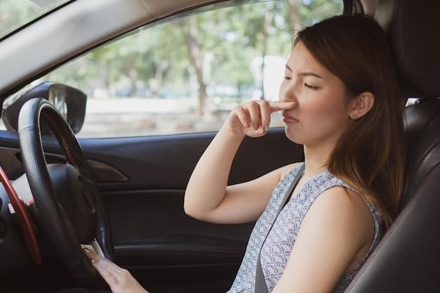 Jeune femme tenant son nez à cause d'une mauvaise odeur en voiture