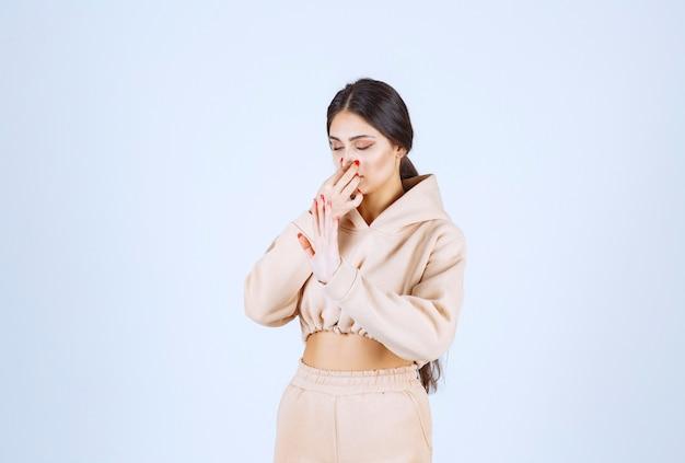 Jeune femme tenant son nez et essayant d'arrêter la mauvaise odeur