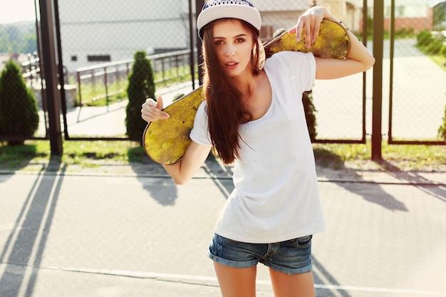 Jeune femme tenant son skate derrière son dos